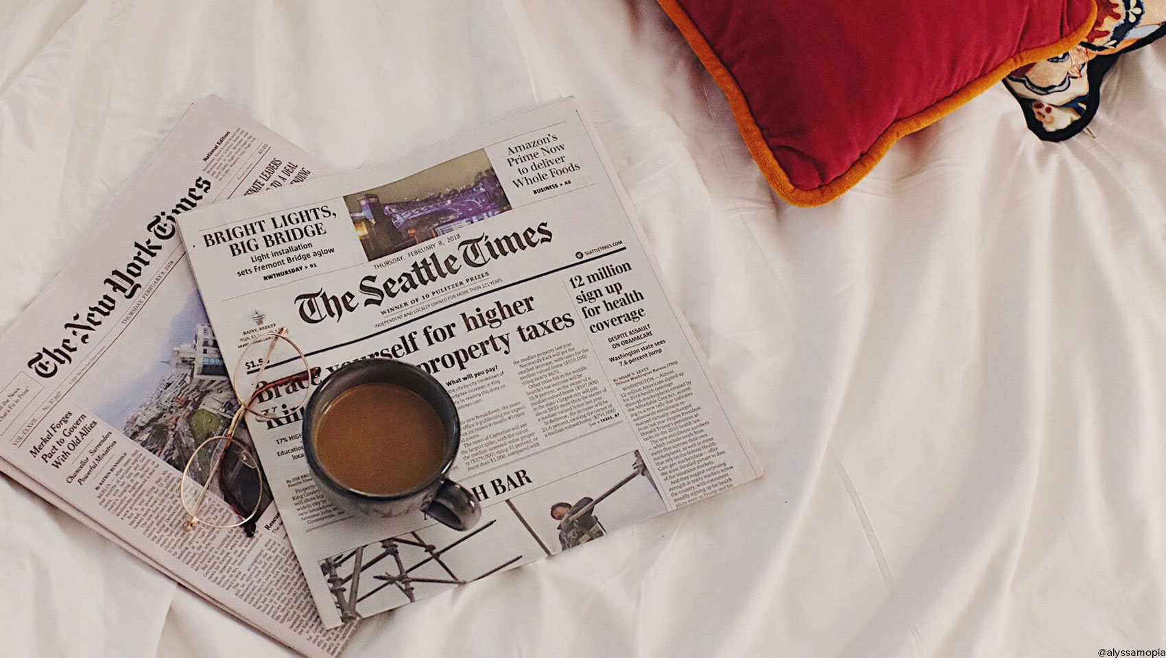 Hotel Monaco guestroom bed with local and national newspaper, cup of coffee and spectacles neatly arranged