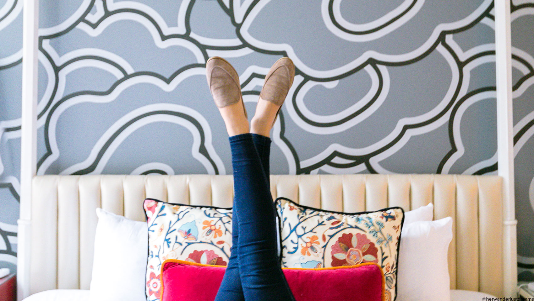 female guest's legs in bluejeans in loafers crossed in the air in the foreground of hotel monaco guestroom cloud motif wallpaper and white bed