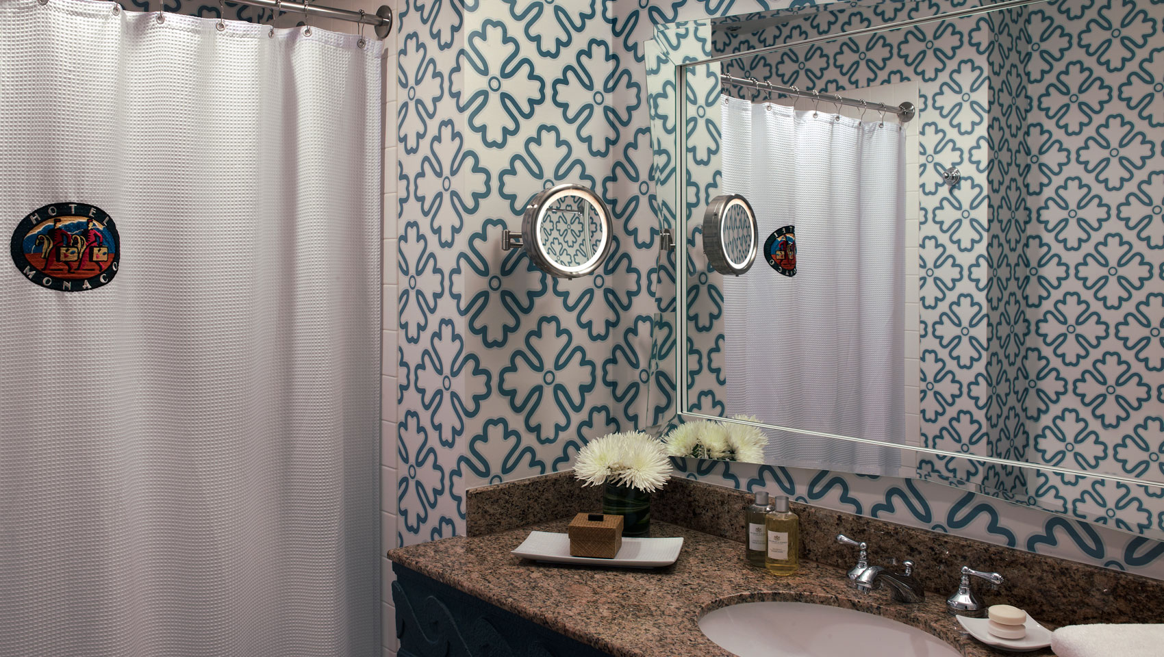 A well-lit vanity mirror surrounded by a brightly patterned wallpaper in the bathroom with luxe amenities and flowers in a vase.