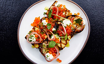 Open face baked potato with fish roe, sour cream, pickled onion and more