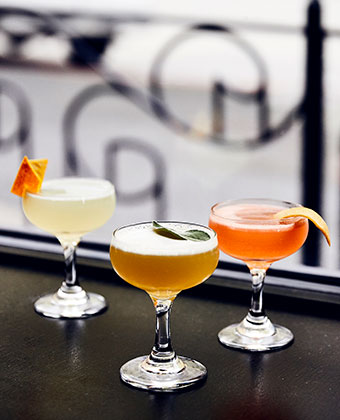 sophisticated cocktails with orange garnishes