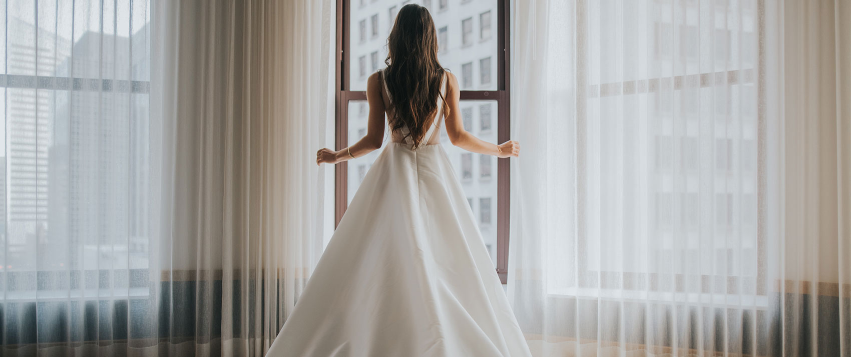 bride standing at window overlooking downtown